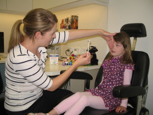 Our head orthoptist Sarita performs a cover test on a young patient